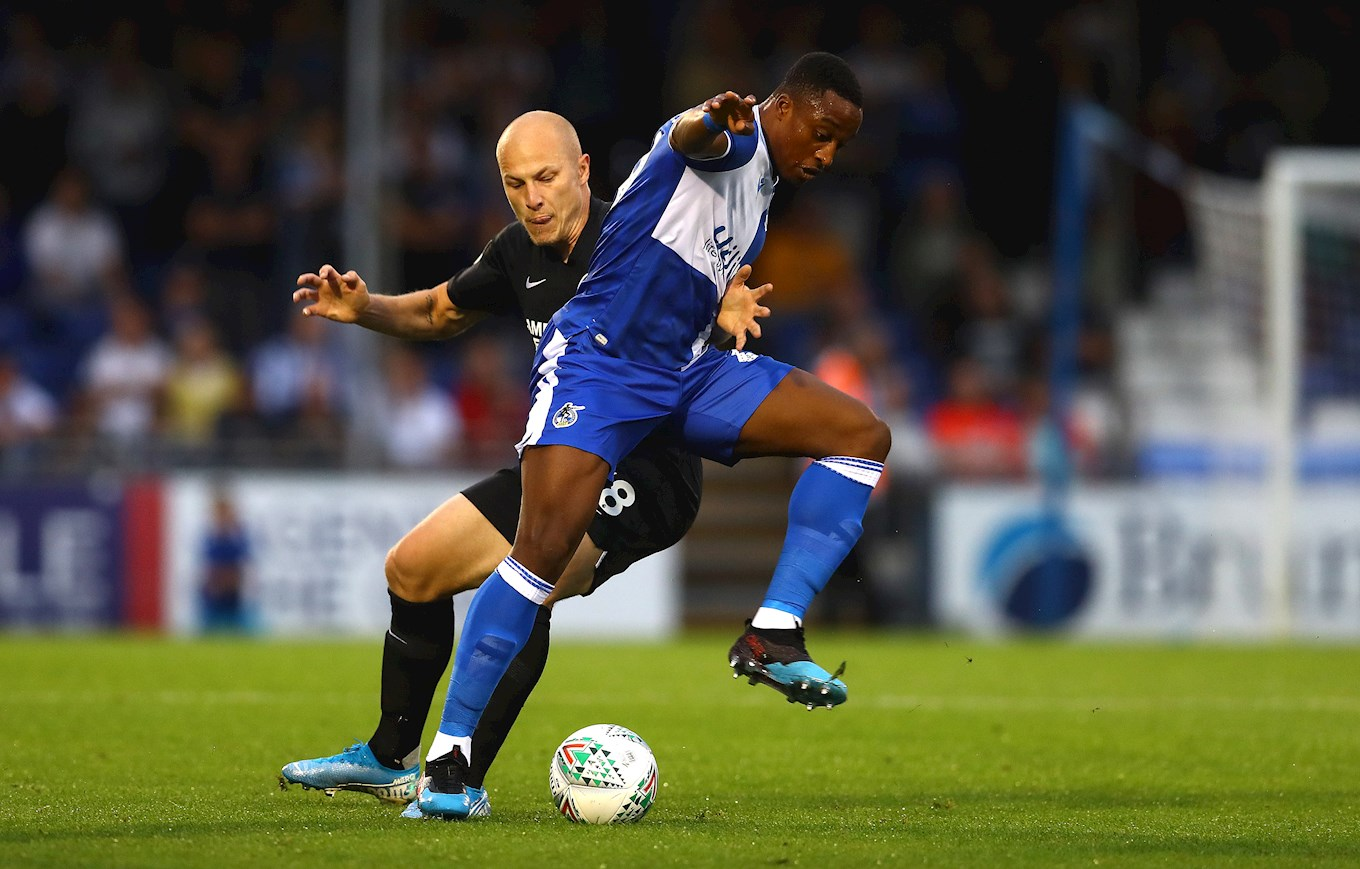 Victor Adeboyejo battles for possession with Aaron Mooy